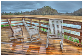 Three rocking chairs on a wooden observatory deck at Grassy Waters Preserve, South Florida