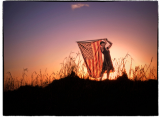 A woman holding an American flag at sunset on Dinner Island Ranch, Florida
