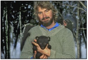 Portrait of photographer Raymond Gehman with three bear cubs on him